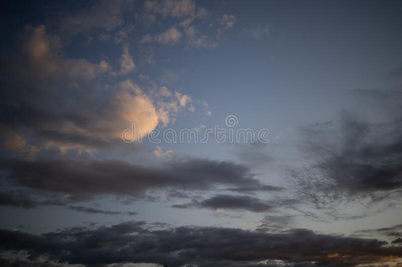 Evening blue sky with dark clouds lit by the orange sun stock images