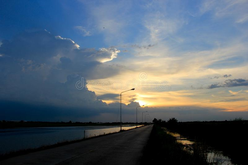 In the evening the blue sky,the sun, shining golden light behind the clouds are gradually moving down view of the street. That stretches as far as the eye can stock images