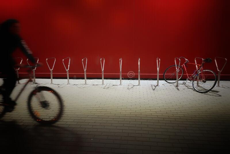 Evening city and bike ride. Night scene. Evening city ride. A passing cyclist on the red background. Wall illuminated with the city lights. Beauty and urban stock photography