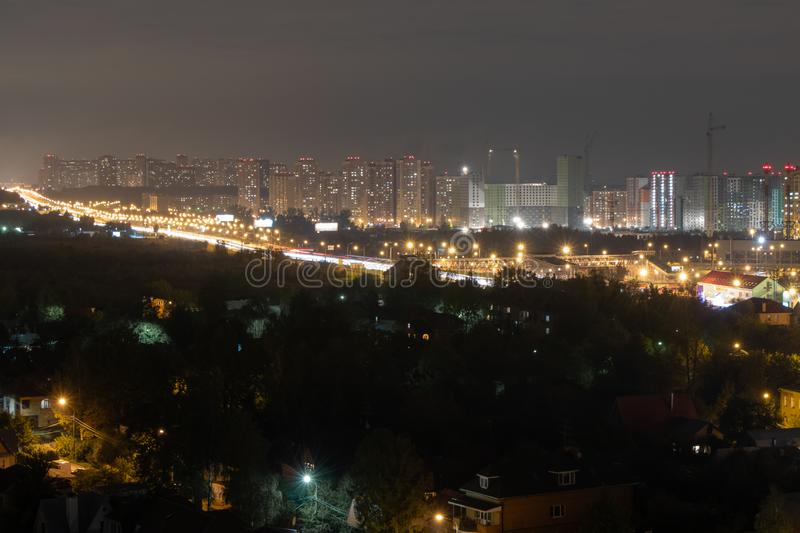 Evening city lights are lit from the windows. Road with a passing vehicle. Construction cranes at night. stock images