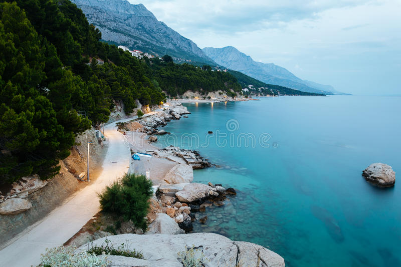 Evening coastline with rocks, trees and mountains in Brela, Croatia at the Adriatic Sea stock photos