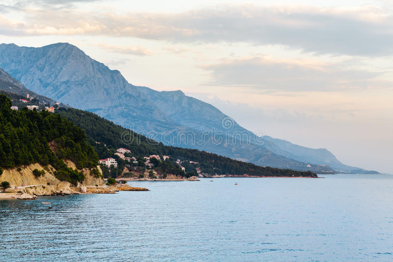 Evening coastline with rocks, trees and mountains in Brela, Croatia at the Adriatic Sea royalty free stock photos