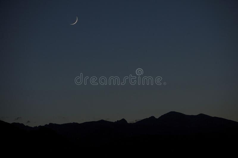 Evening Crescent Moon in the shadow of the mountains. Rockymountains, gstyleartist, landscapephotography, colorado royalty free stock images