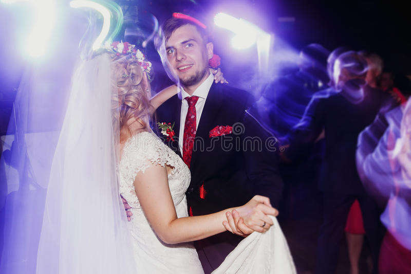 Evening dance party - newlywed bride and groom dancing at wedding reception ballroom, surrounded by colorful neon lights royalty free stock photos