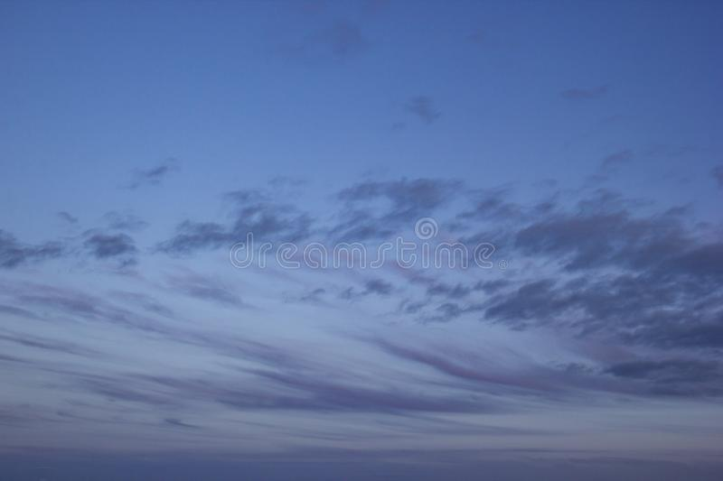 Evening Dark Blue Sky Covered With Stripes of Violet Clouds royalty free stock photo