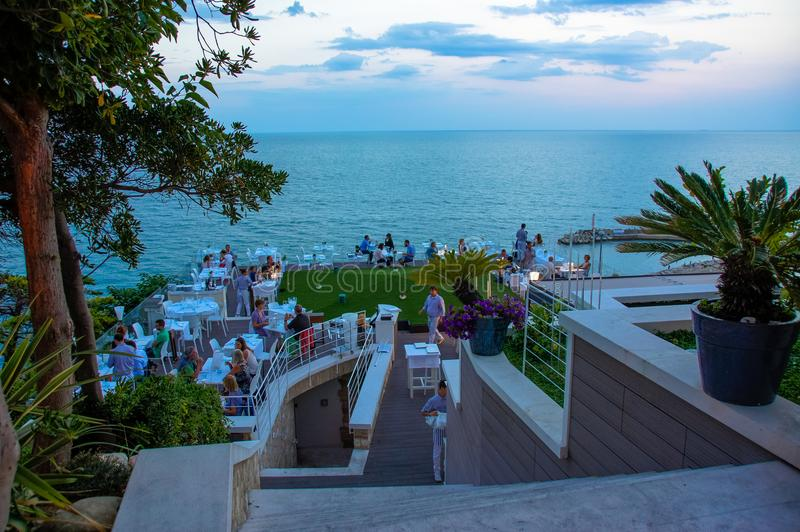 Evening dinner in a restaurant overlooking the sea. View on the Adriatic coast in Numany, Italy. royalty free stock photography
