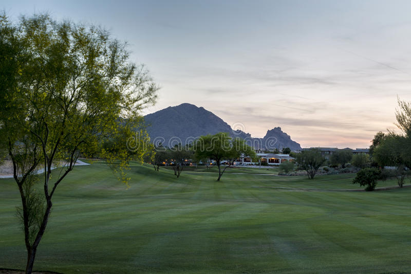 Evening falls over the Scottsdale Greenbelt Park and Camelback Mountain. Evening falling over the Scottsdale Greenbelt with grass and Palo Verde and Mesquite stock image