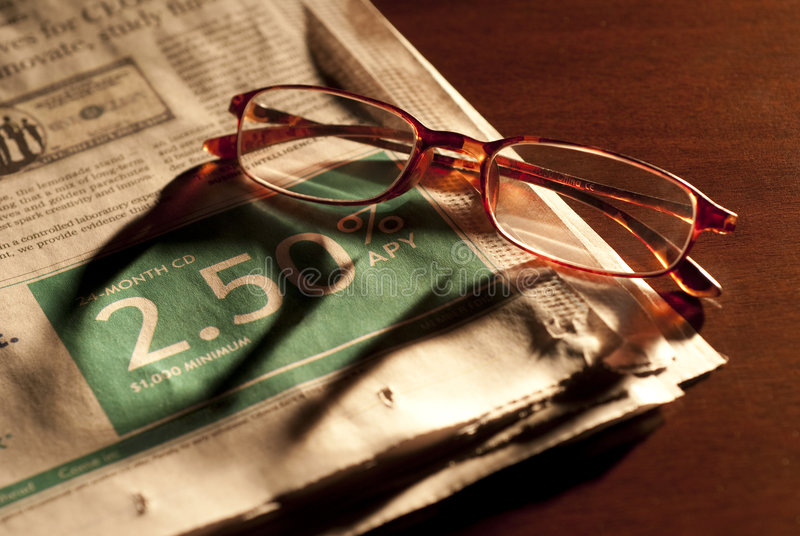 Evening finance. Glasses over business section of the paper lit by table lamp stock photos