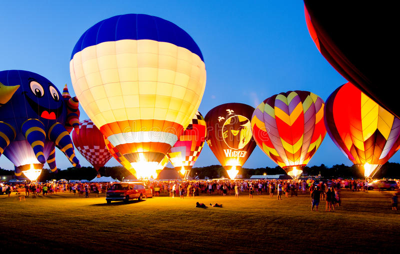 Evening Glow Hot Air Balloon Festival. Hot air balloons lighting the night sky during an evening glow spectator event at the 2015 Hot Air Balloon Festival in royalty free stock image