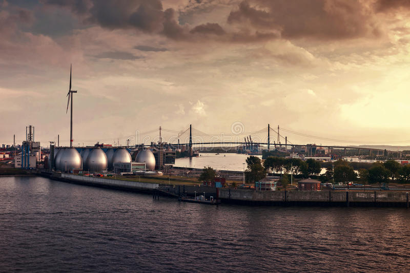 Evening in the Hamburg harbor. Evening in the port of Hamburg with Köhlbrand-bridge and the egg-shaped digesters of sewage treatment plant Köhlbrandhöft royalty free stock photography