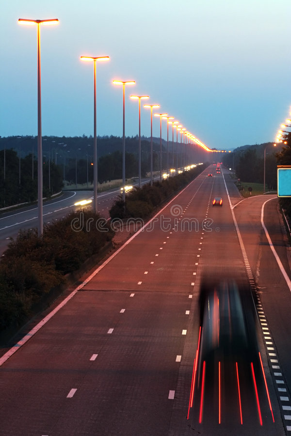 Evening highway. Street lamps and car headlights are illuminated; blurred cargo truck on the foreground stock photography