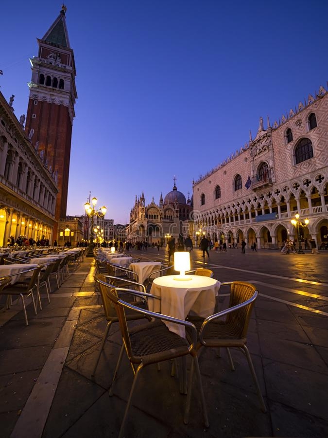 Evening hours in Venice. A picture of San Marco Square in Venice with a detail fo a restaurant table in evening hours stock photo
