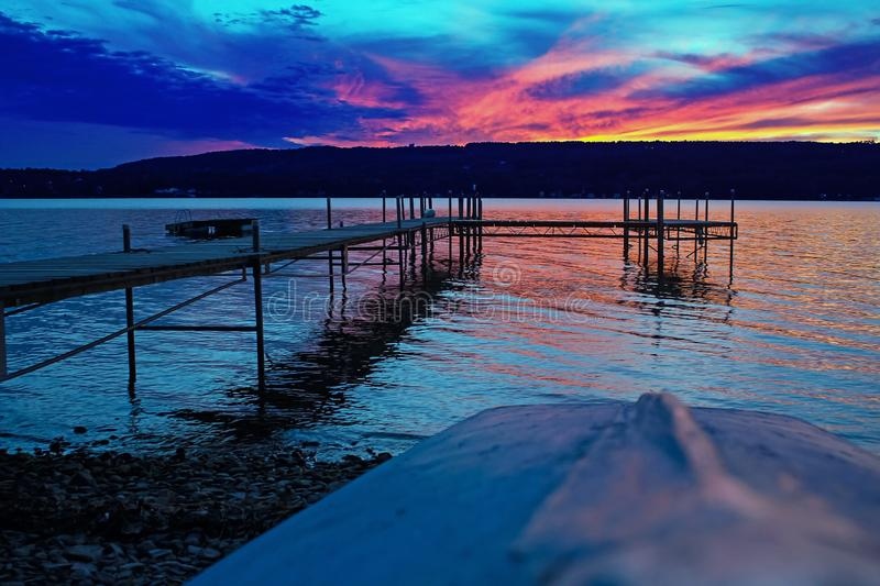 Evening at the Lake with Dock Prominent and Boat in Foreground, Keuka Lake, Penn Yan, New York, August, 2012. Evening at the Lake with Dock Prominent and Boat in royalty free stock image