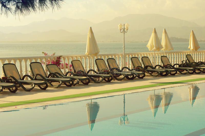 An evening landscape with beach umbrellas near the pool. stock photography