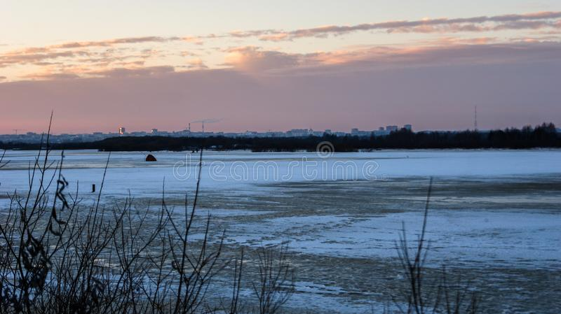 Evening landscape by the river in winter begins to melt the ice, over the horizon you can see the city. The evening landscape by the river in winter begins to stock photography