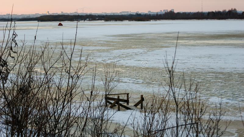 Evening landscape by the river in winter begins to melt the ice, over the horizon you can see the city. The evening landscape by the river in winter begins to royalty free stock photos