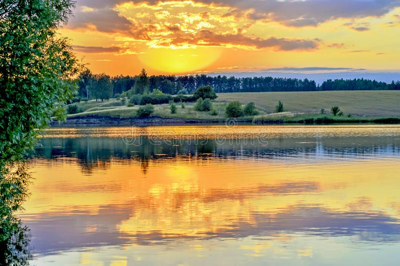 Evening landscape screensaver on the lake with the reflection in the water of the evening sky filled with sun. Background stock image