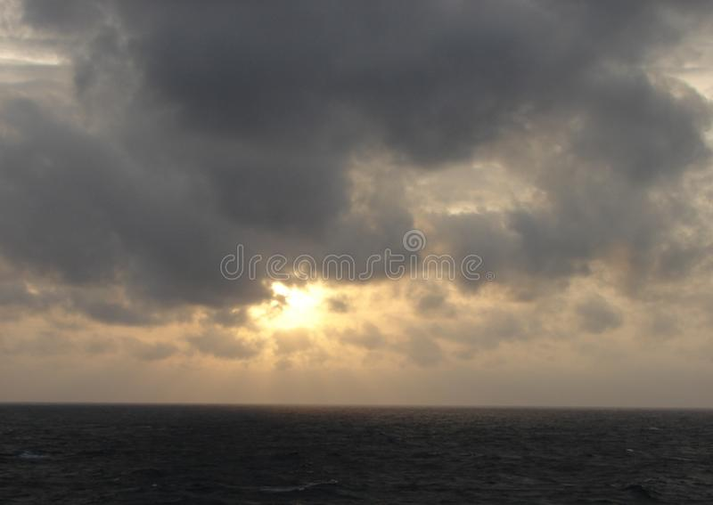 Evening landscape. Sea, sunset through the clouds and cloudy sky in the photo. Sea background royalty free stock images