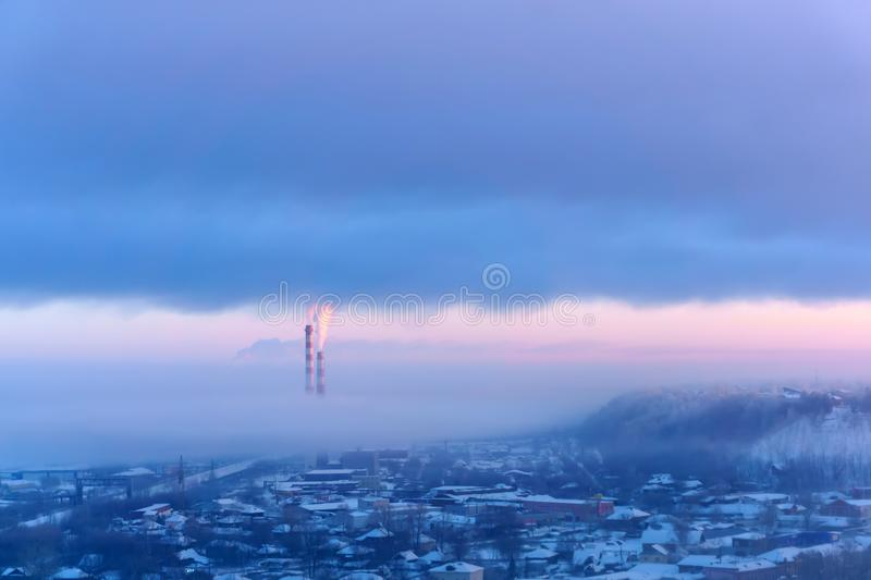 Evening landscape of a winter industrial zone with smoking chimneys stock photos
