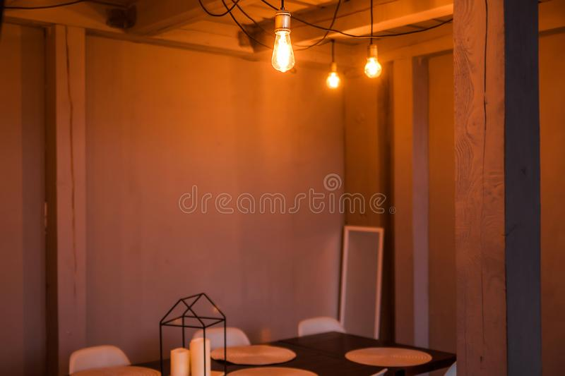 The evening light from the light bulb illuminates the wooden dining table and chairs. Photo of The evening light from the light bulb illuminates the wooden royalty free stock photos