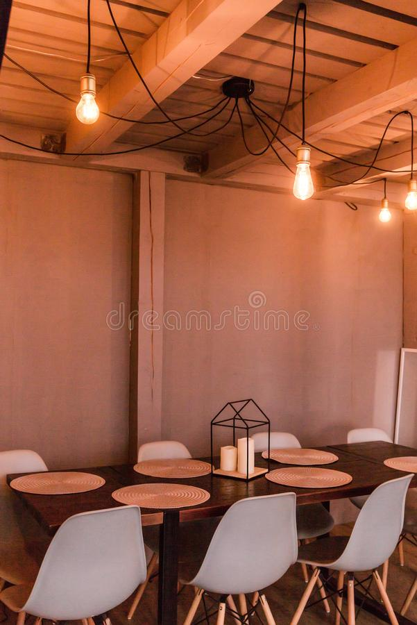 The evening light from the light bulb illuminates the wooden dining table and chairs. Photo of The evening light from the light bulb illuminates the wooden royalty free stock photo