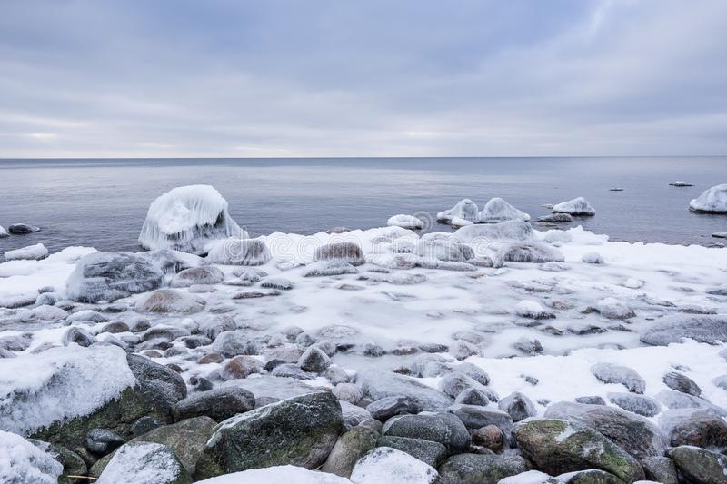 Evening light and icy weather on shore like fairy tale country. Rocky beach on wintertime. Evening light and icy weather on shore like fairy tale country stock photos