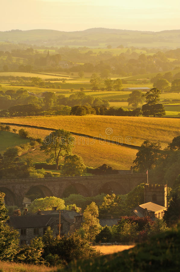 Evening light, Ingleton, North Yorkshire. The last light of the day, illuminating the fields and meadows, around Ingleton village church and viaduct, in north royalty free stock photography