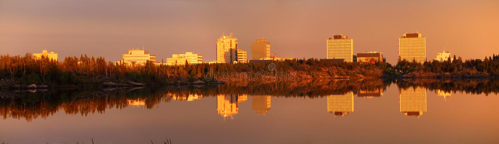 Evening Light mirrors Downtown Yellowknife in Frame Lake, Northwest Territories, Canada. Filtered through a light rain shower, the light of the setting sun royalty free stock images
