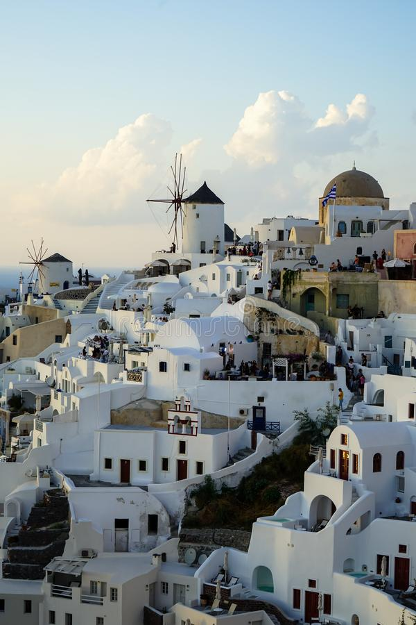 Evening light scene of Oia windmill and white building townscape along island mountain facing ocean with soft cloud and light blue royalty free stock images