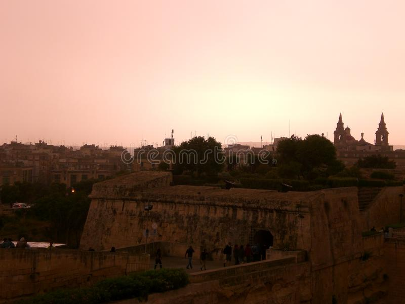 Evening light in Valletta, Malta. Pink evening light over Valletta, Malta. City ruins in the foreground and historic buildings in the distance royalty free stock photos