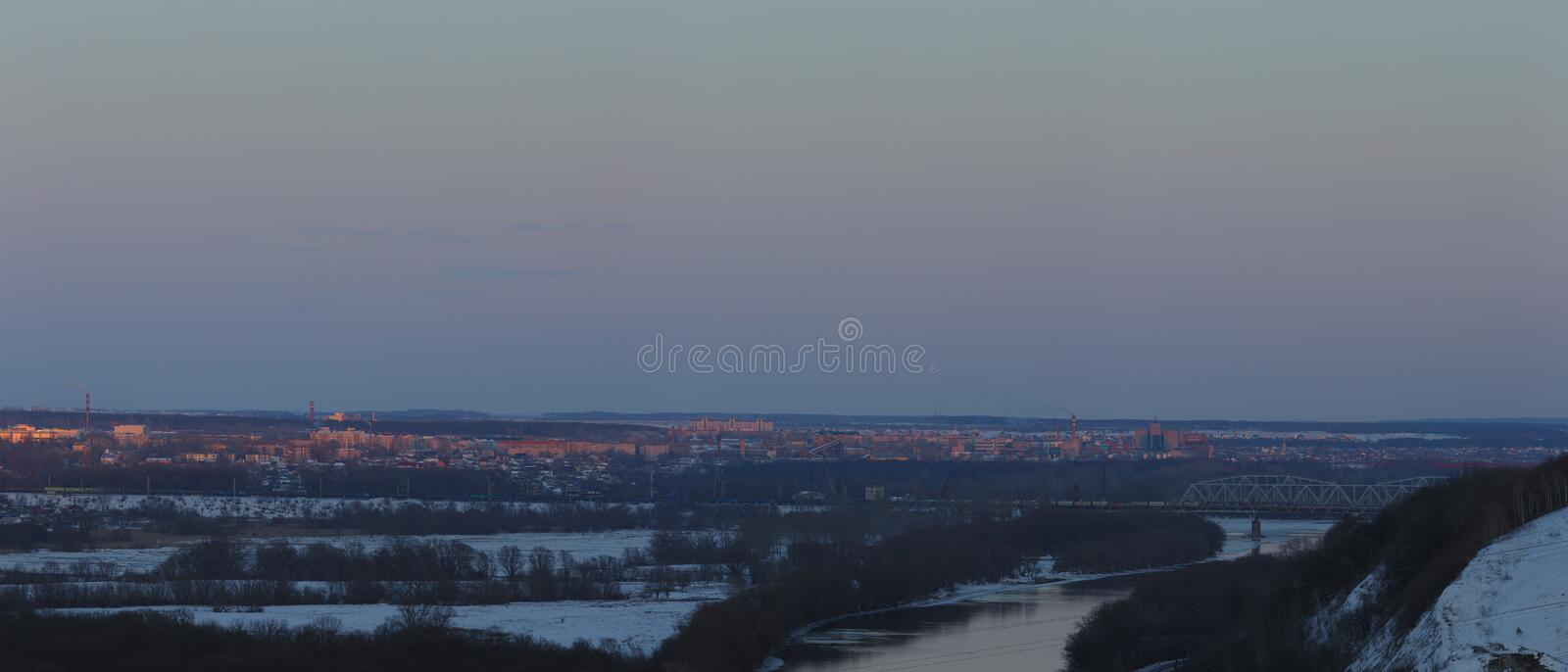 Evening lighting over the city. Sunset time in the twilight sky. Panoramic top view of residential district.  stock photos