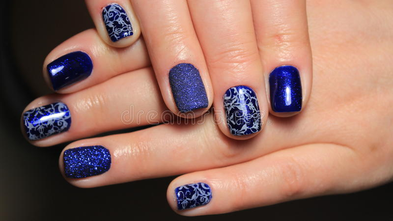 Evening manicure, design cold colors, blue gel polish with silver ribbons and pattern. Nails stock photo