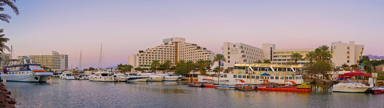 The evening in marina of Eilat. EILAT, ISRAEL - FEBRUARY 23, 2016: The view from the bridge on the wide marina and the tourist neighborhood, located around it stock photo
