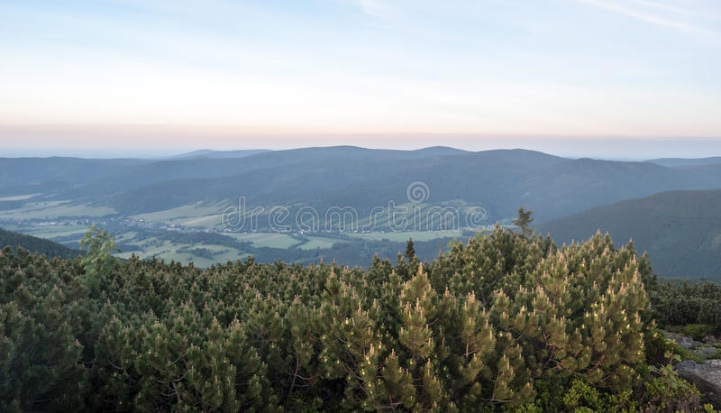 Evening mountain panorama with hills, valley with villages and clear sky stock photo