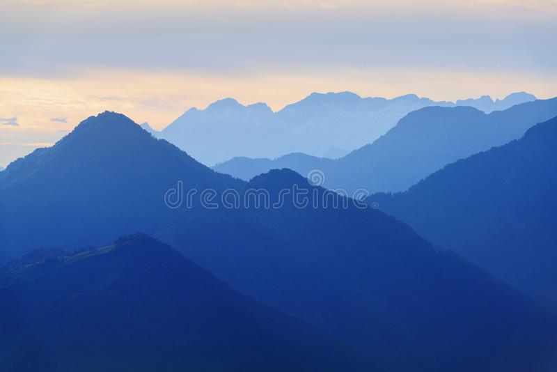Evening mountains in blue tonality. Beautiful calm evening mountains silhouettes in blue tonality stock images