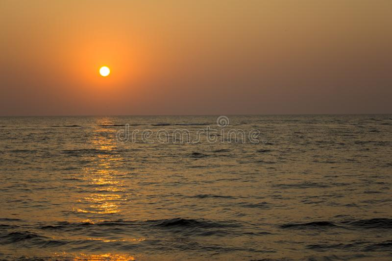 Evening ocean with a sun path and waves against the backdrop of a dark yellow, purple sunset sky stock image
