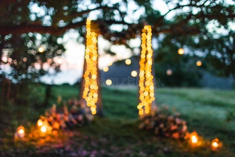 Evening outdoor party blurred lights background. Evening outdoor party or night fair festival with blurred lights bokeh for background usage. Wedding arch stock image