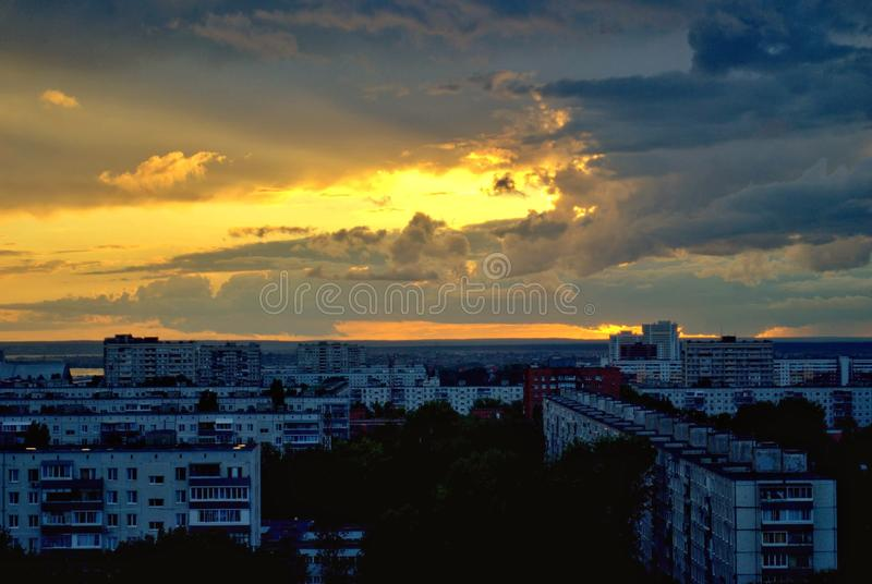Evening panorama of the city against the background of a sunset sky and clouds. stock photography