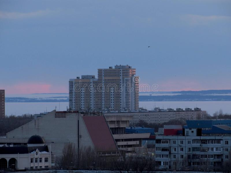 Evening panorama of the city overlooking the residential buildings and the frozen Volga River in the background. Evening panorama of the city of Togliatti stock photography