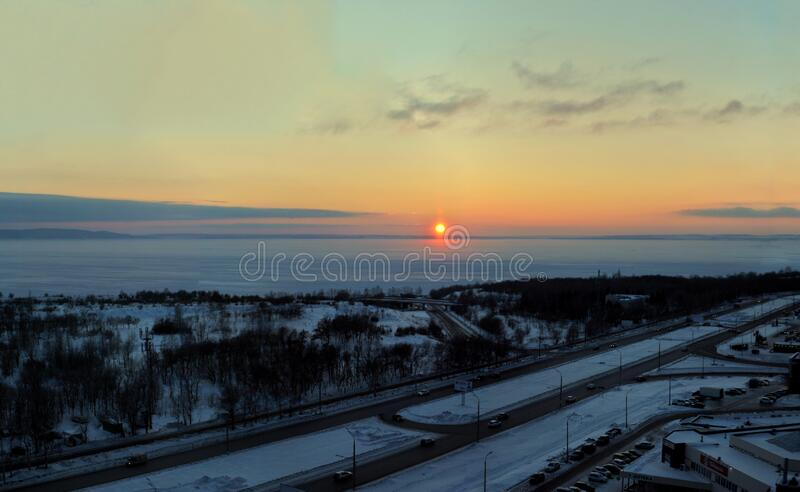 Evening panorama of the embankment of the frozen Volga River against the backdrop of a stunning sunset sky and clouds. stock images