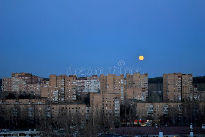 Evening panorama of a residential quarter of the city on the background of a rising full moon. stock photos