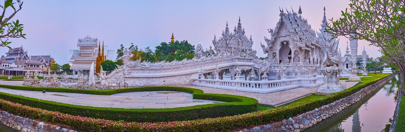 Panorama of White Temple and Rebirth Cycle bridge, Chiang Rai, Thailand. Evening panorama of White Temple complex with narrow moat, topiary garden, Rebirth Cycle royalty free stock image
