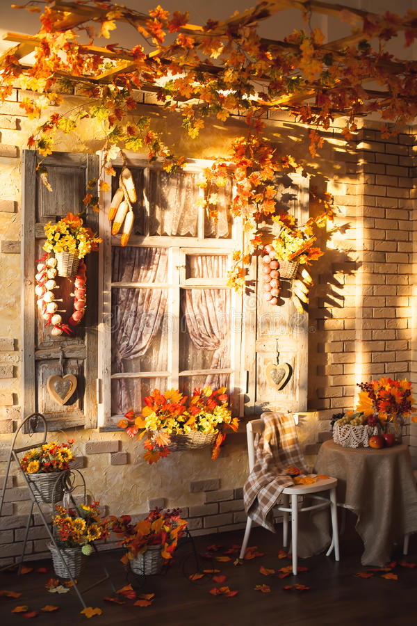 Evening patio. Window with vintage shutters decorated with autum. N vegetables. Yellow leaves everywhere, at the center two chairs and a table with burlap royalty free stock photo