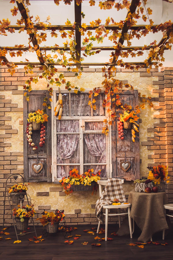 Evening patio. Window with vintage shutters. Decorated with autumn vegetables. Yellow leaves everywhere, at the center two chairs and a table with burlap royalty free stock photos