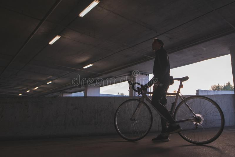 An evening photo of a young cyclist standing under the bridge with a bicycle stock photography