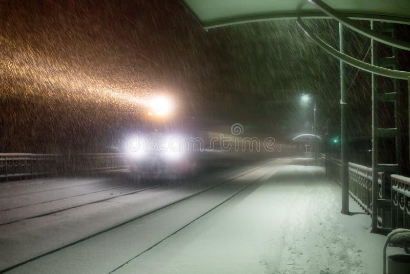 Evening pociąg przyjeżdża przy stacją snowfall obrazy stock