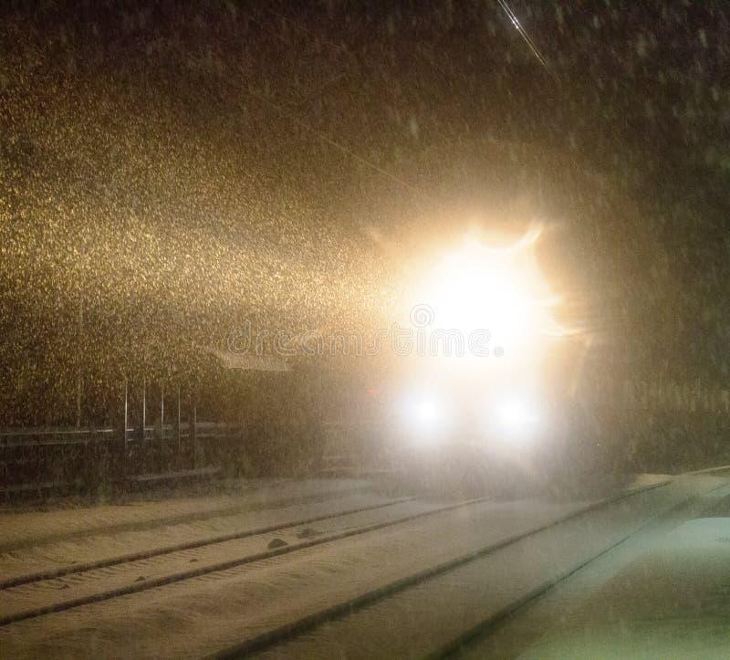 Evening pociąg przyjeżdża przy stacją snowfall obraz stock