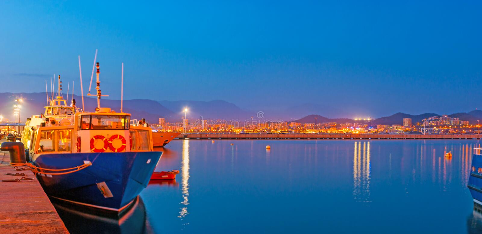 Evening in port of Ajaccio. The bright city lights reflect in calm waters in port of Ajaccio, Corsica, France stock image