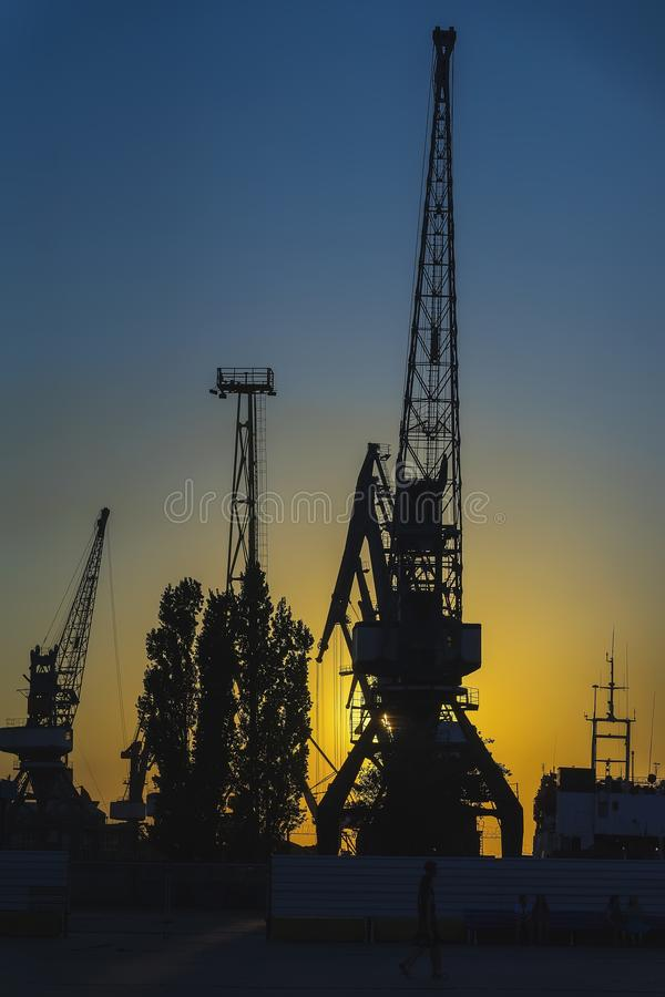 Evening in the port, sea, river dock. Silhouette of industrial cranes. Wharf, Port landscape. Bright sunset stock image
