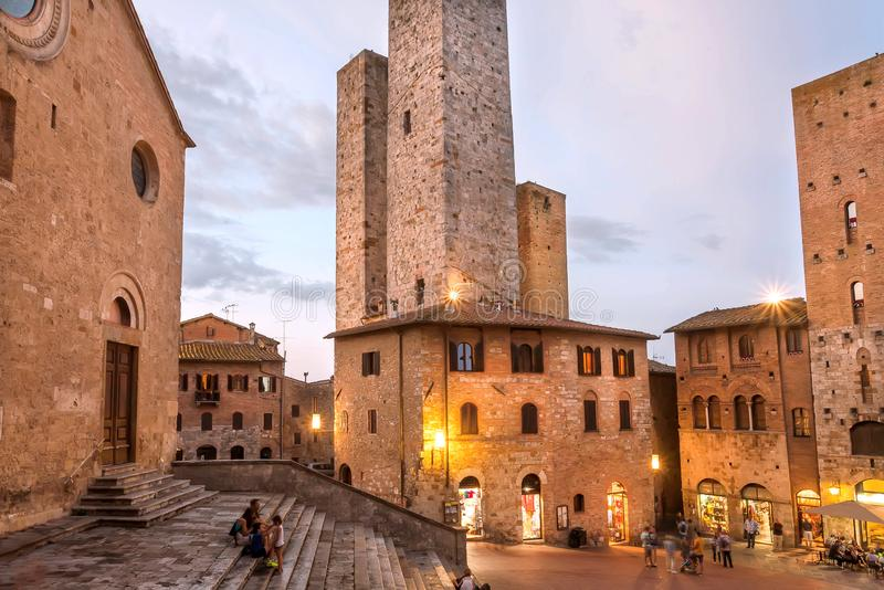 Evening with relaxing people under brick towers of ancient town of Tuscany royalty free stock photos